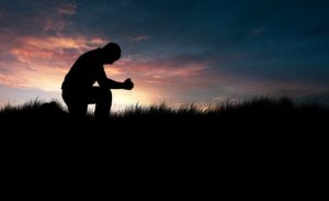 Man praying in the grassy field